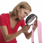 Private investigator woman looking through magnify glass at a neck tie