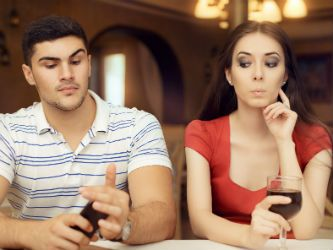 Couple each on their cell phone looking for information about how to know if your spouse is cheating