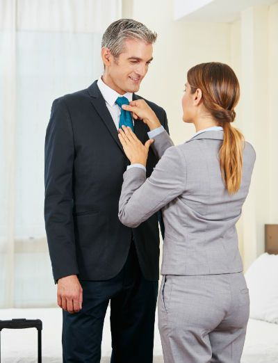 Business traveler having tie staightend by woman in hotel room